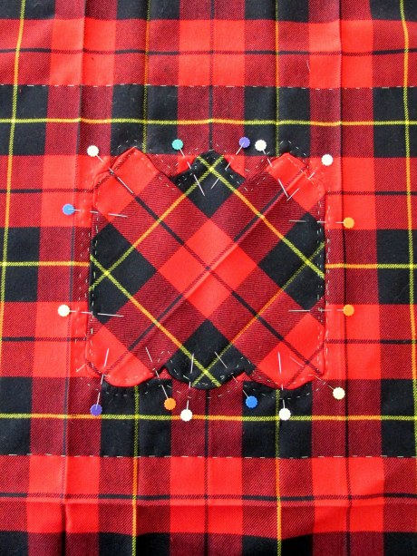 "After a whole whack of basting around the edges the pieces are pinned together.  The section for the boteh was cut at 90 degrees so that the tartan could be inserted ""at odds with itself"""